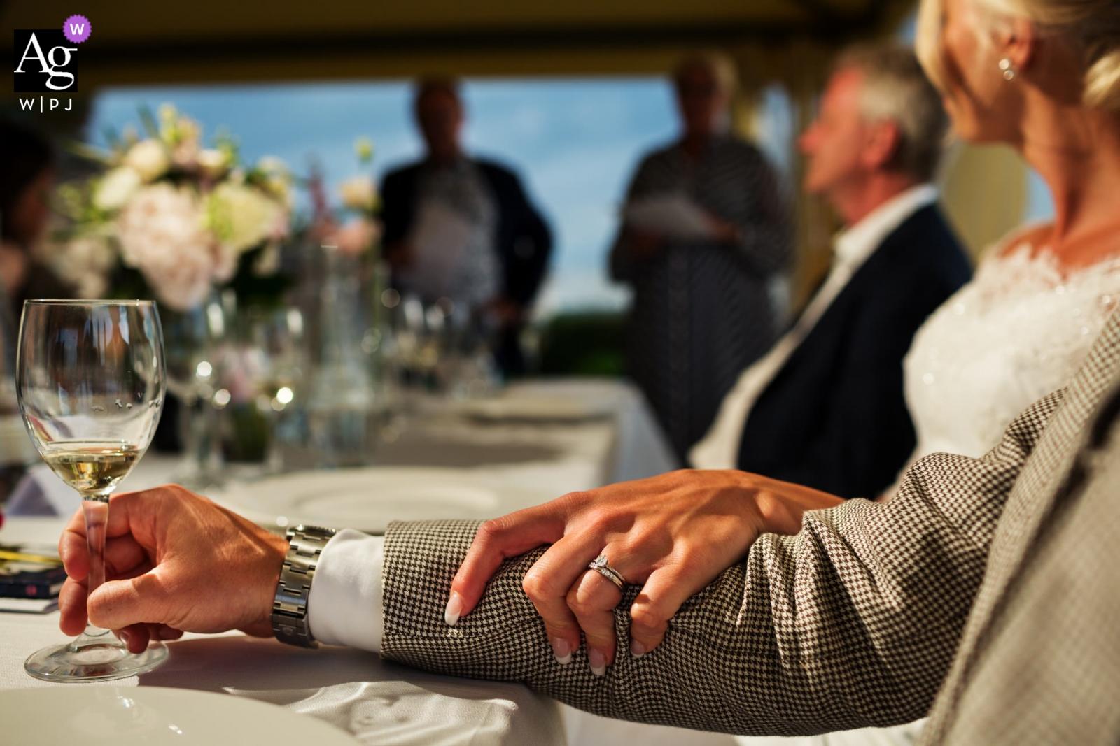 托斯卡納創意婚紗攝影| 拿著新郎的胳膊的新娘細節,顯示她的圓環