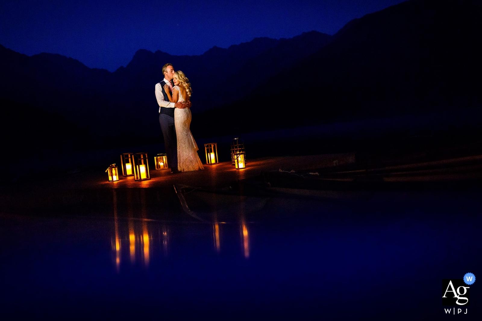 Kreative Hochzeitsportraitfotografie Colorados der Braut und des Bräutigams mit den Laternen reflektierte sich am Wasser / am See