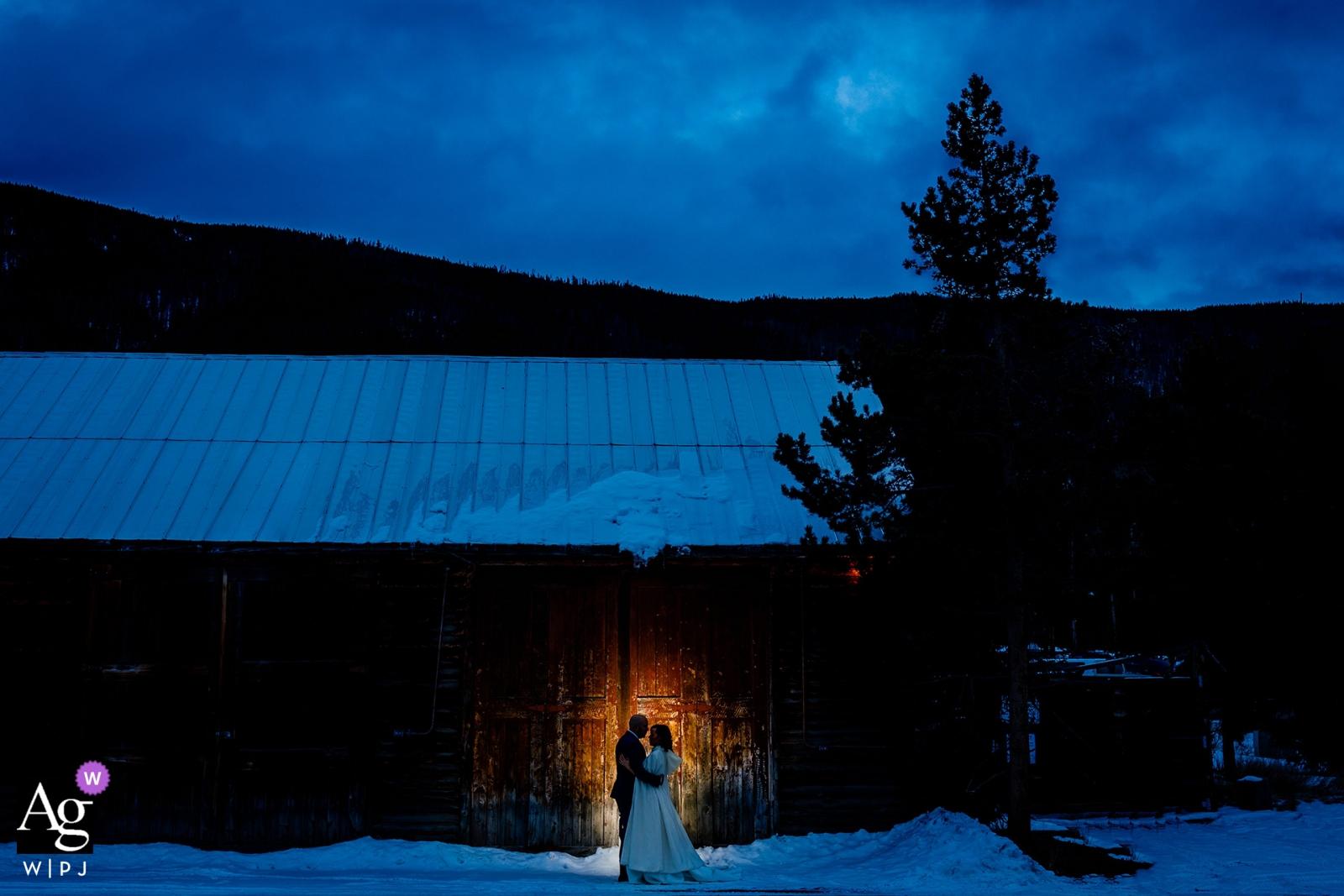 Colorado-Hochzeitstagbraut- und -bräutigamporträt im Schnee an der Dämmerung gegen eine beleuchtete Scheune