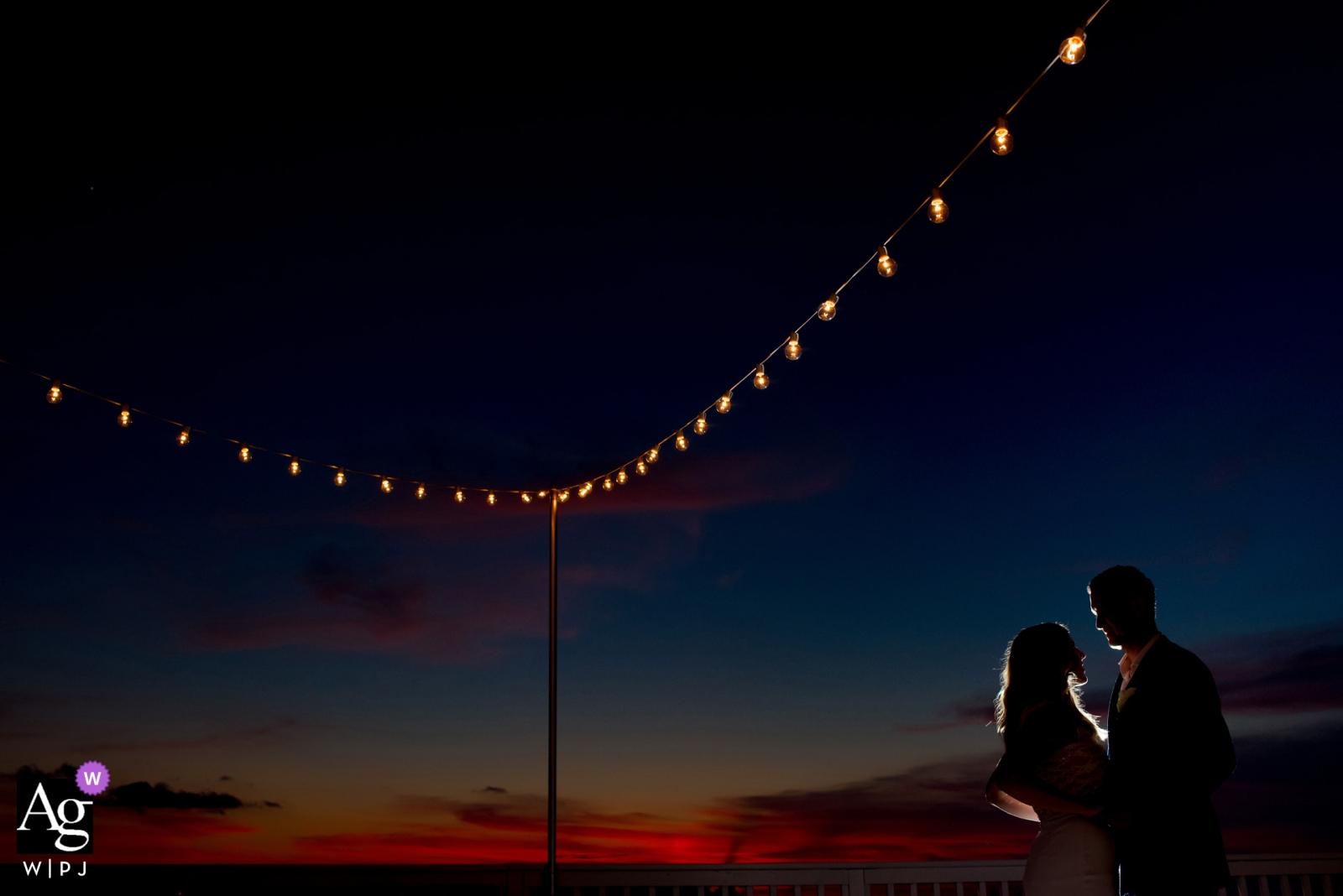 Portrait de couple jour de mariage à Key West sous une chaîne de lumières de réception au crépuscule