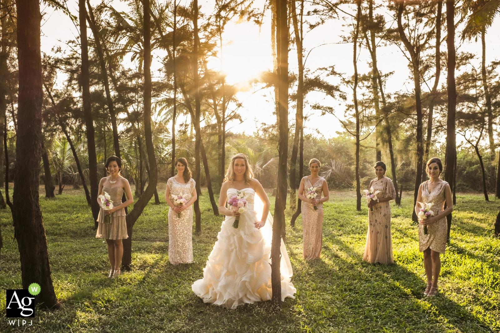 Photographie de mariage à Goa - Mariage / demoiselles d'honneur avec photo de la mariée dans les arbres sur l'herbe