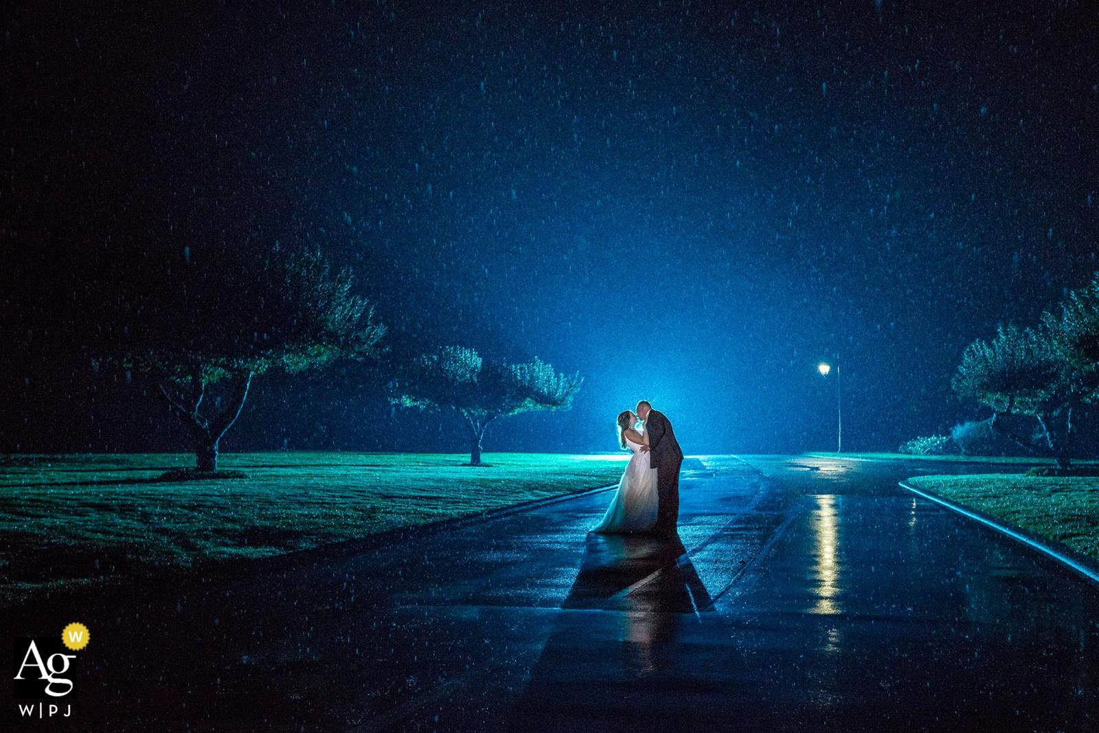 séance de portrait en soirée avec mariage des mariés de la Colombie-Britannique sous la pluie sur la chaussée mouillée