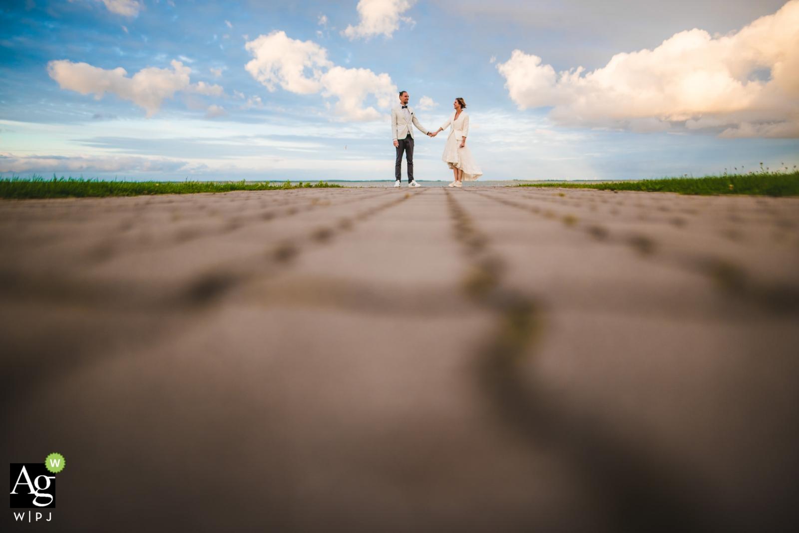 Photographie de portrait de mariage créatif de Washington DC de jeunes mariés | portrait d'angle faible avec passerelle de briques ciel bleu et nuages