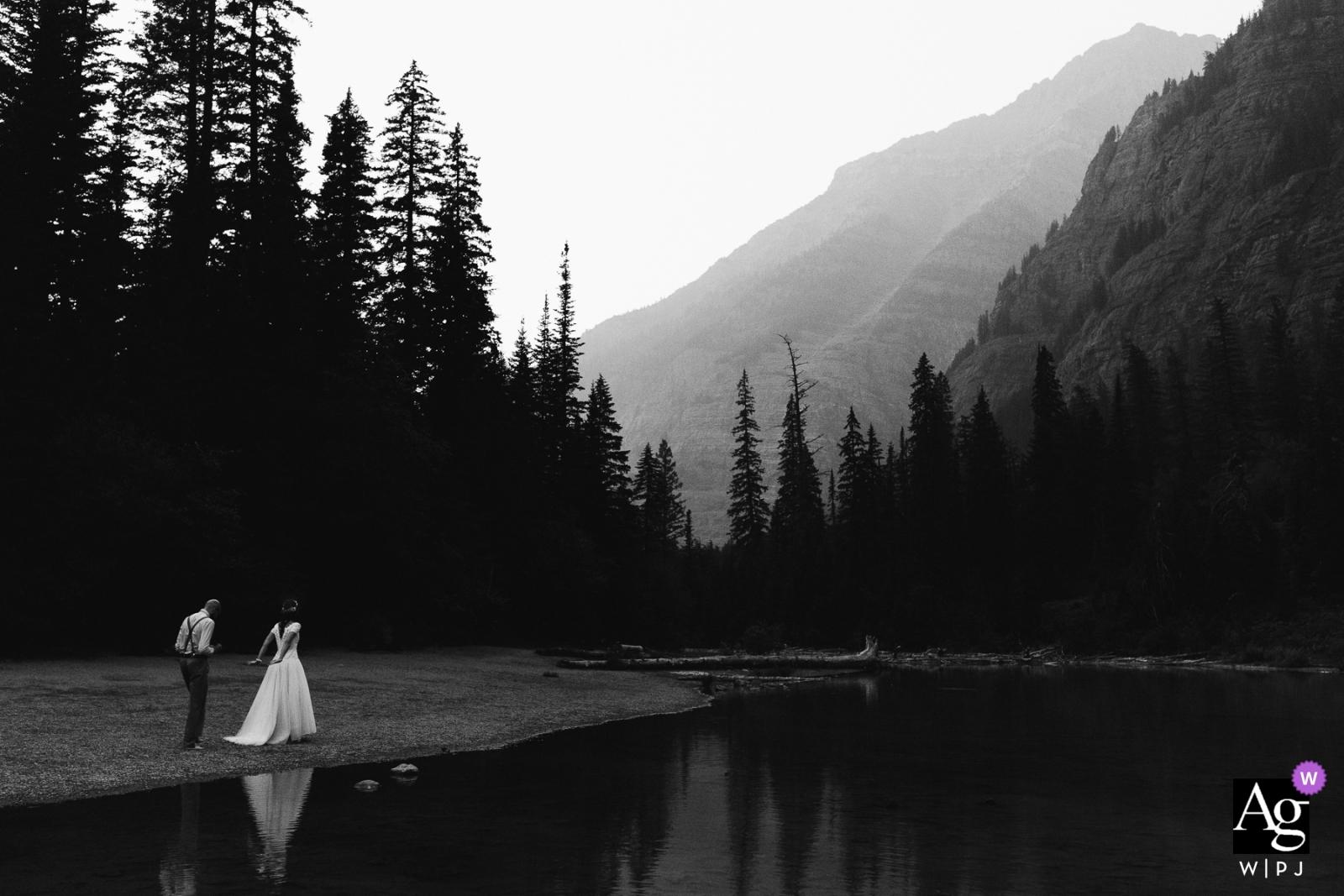 Retrato de pareja del día de boda de Montana en blanco y negro con lago, árboles y montañas
