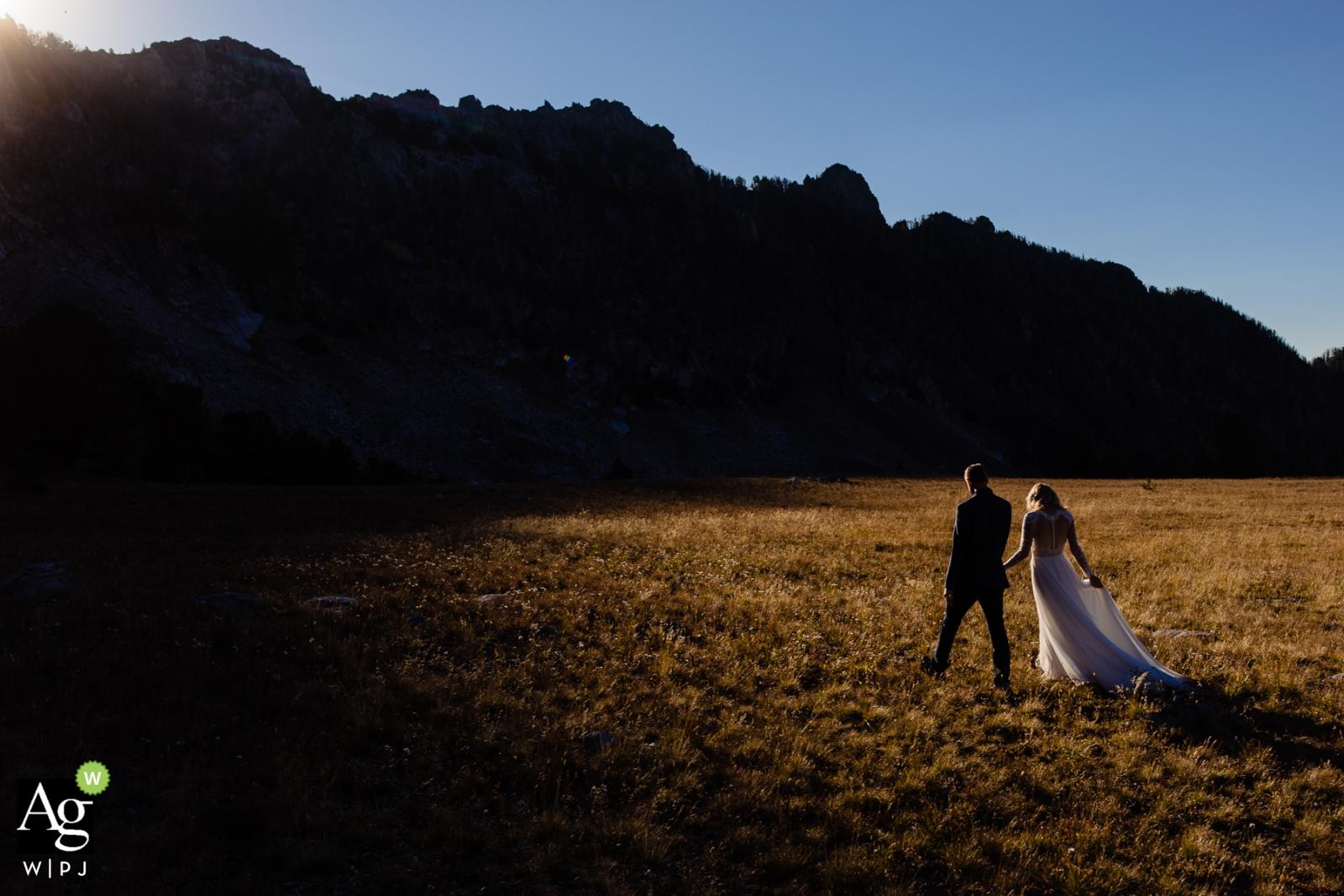 Photos de mariage créatives et artistiques de Missoula d'un couple marchant au coucher du soleil dans des champs - par un photographe du Montana
