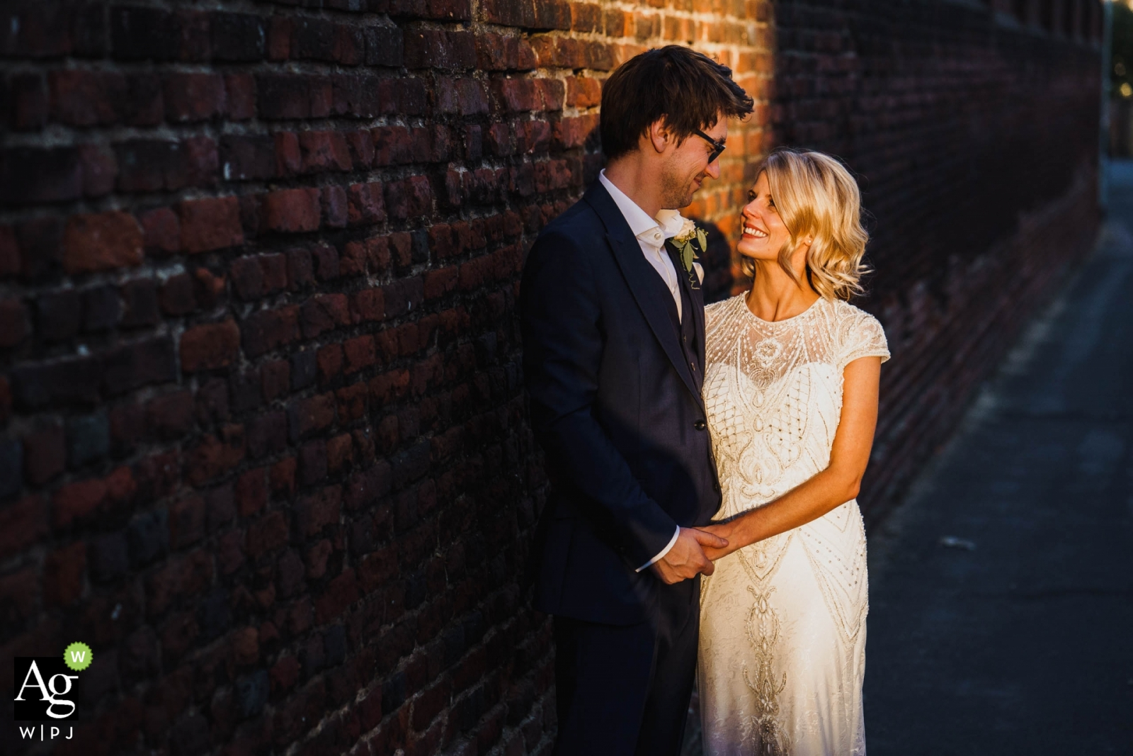 artistic wedding pictures of a Norfolk bride and groom in sunlight against brick wall in alley