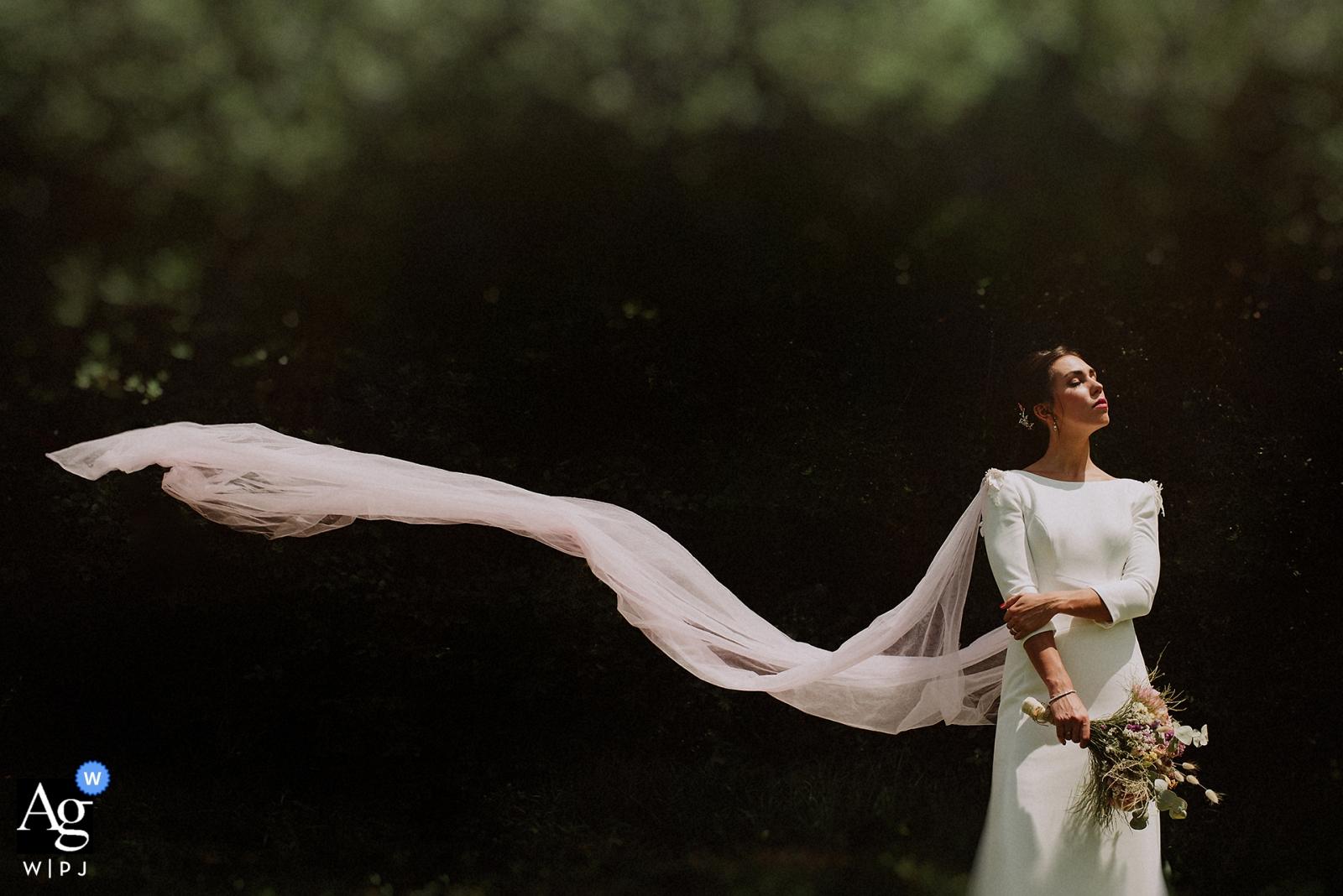 Gipuzkoa-Porträtfotoaufnahme-Sitzung der Braut draußen mit fließendem Schleier im Wind