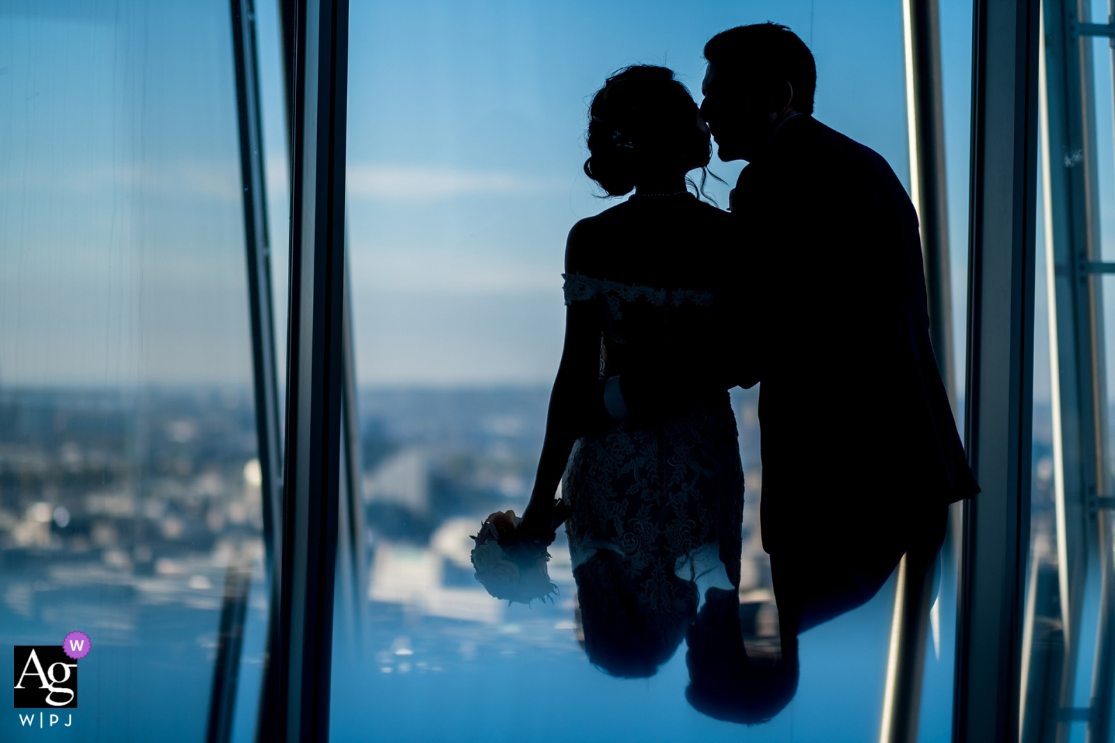 Bedfordshire, England destination wedding reception photograph of bride and groom kissing near window with a view of the city in blue