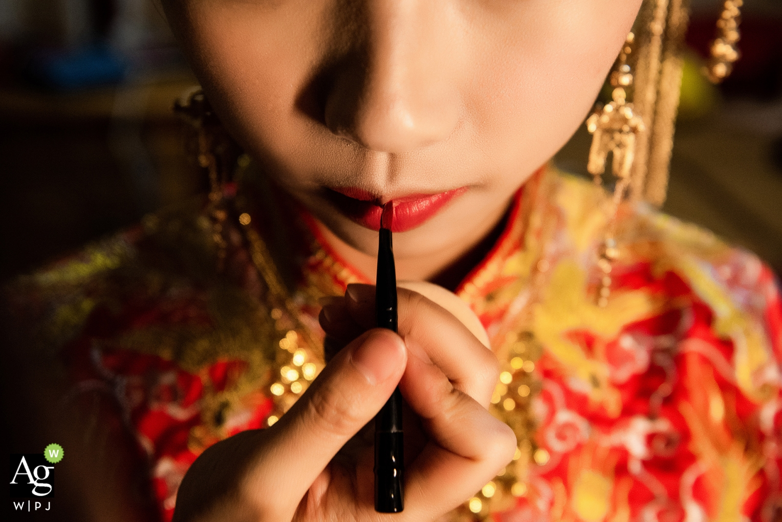 Fujian, China detail of lipstick being applied to bride's lips