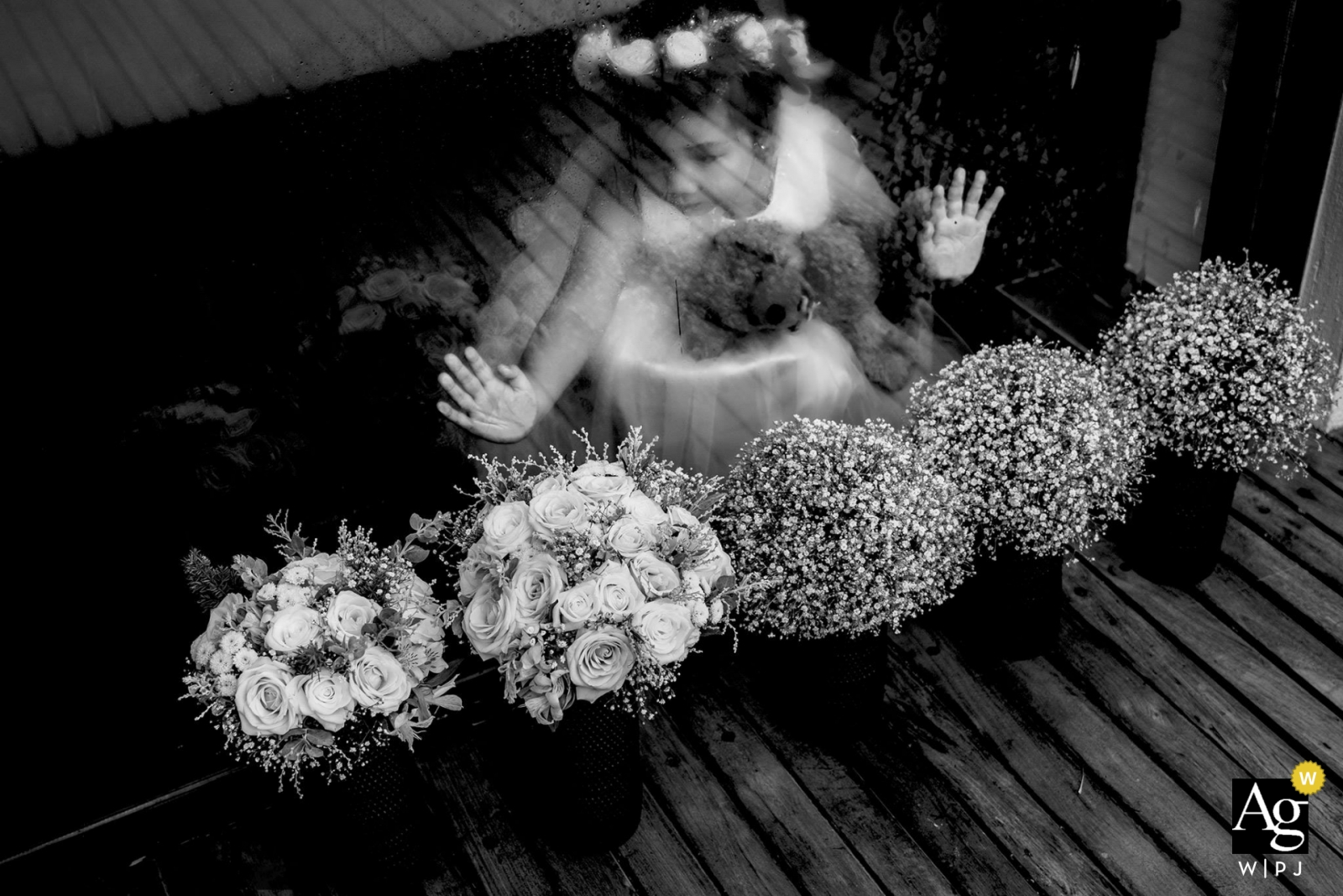 nha trang wedding photographer | the flower girl looks through the glass window at five bouquets