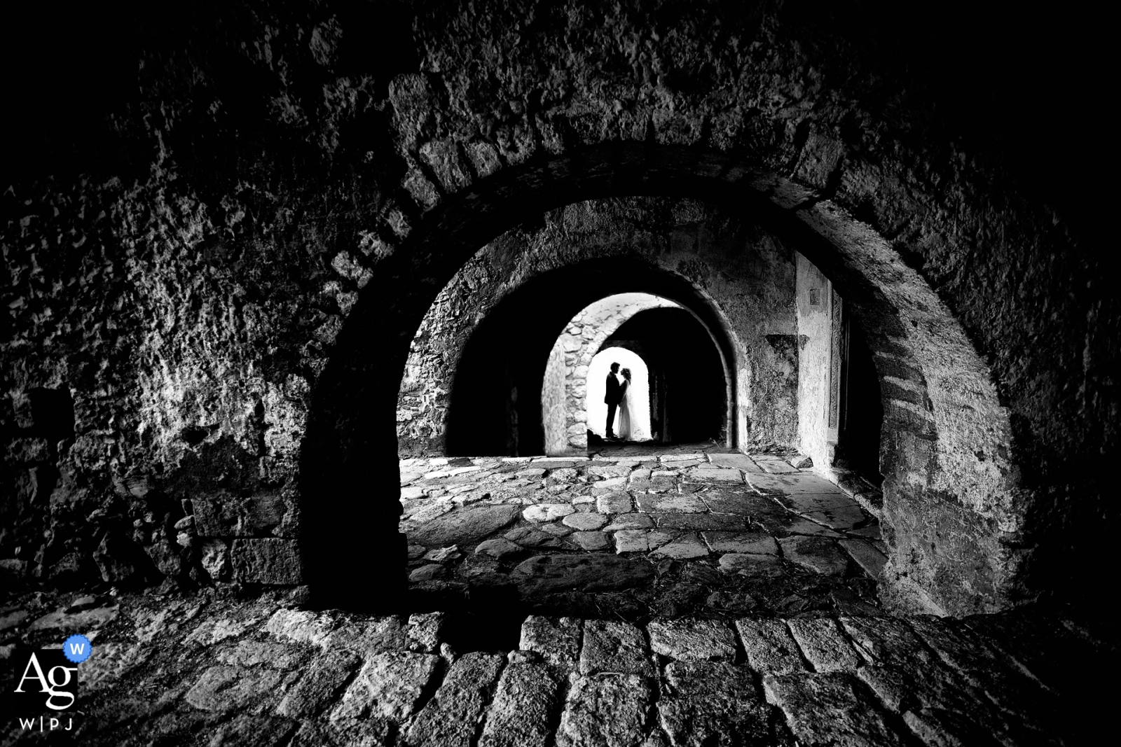 Wedding Photos in Monemvasia, Greece | Black and white portrait with the couple under stone arches
