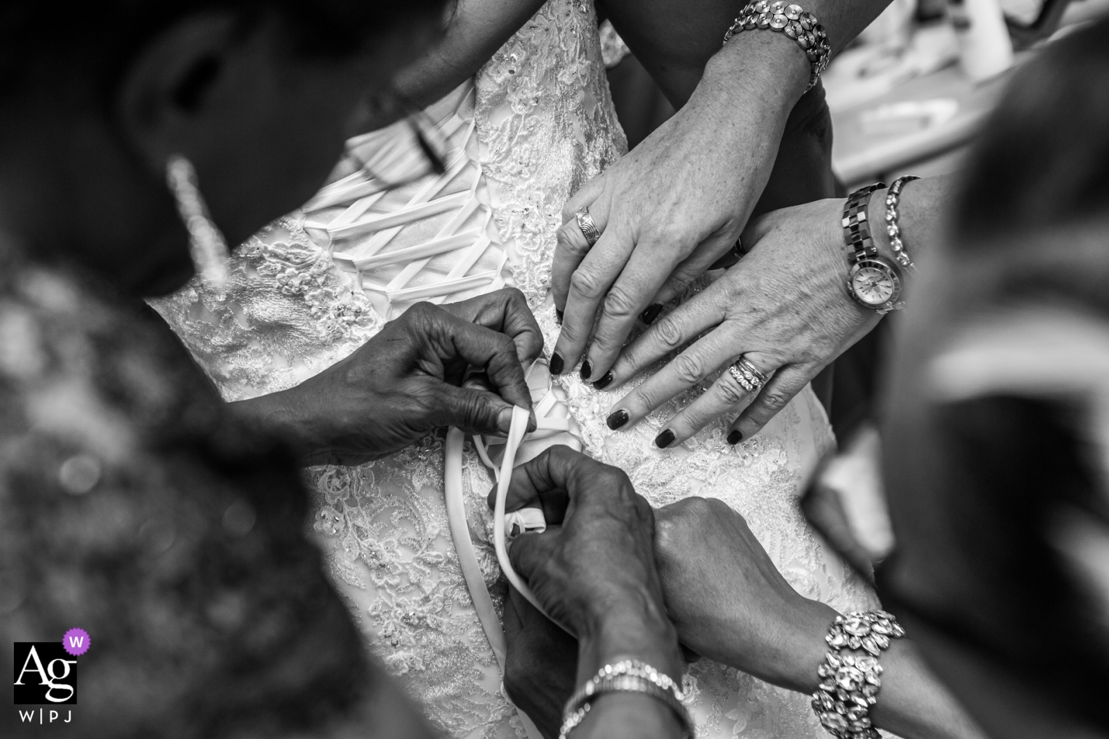 London bridal prep photograph of the back of the bride's dress with many hands helping