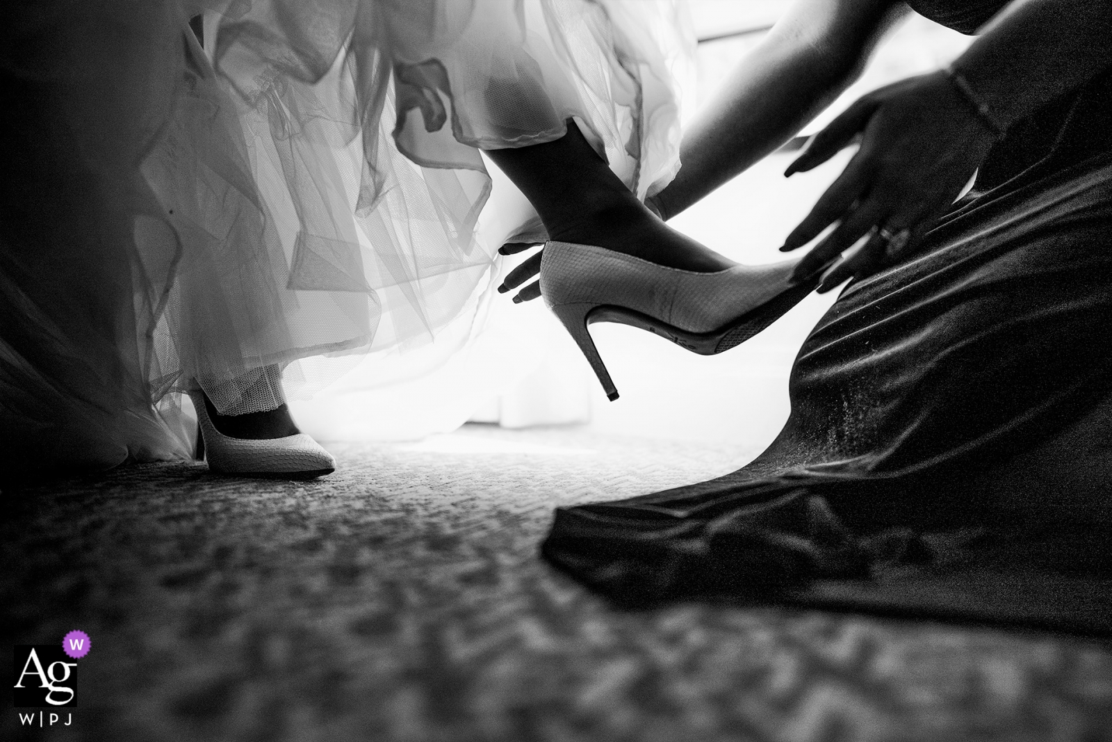 The bride receives help putting on her shoes at the Battery Gardens, New York | artistic wedding photographer