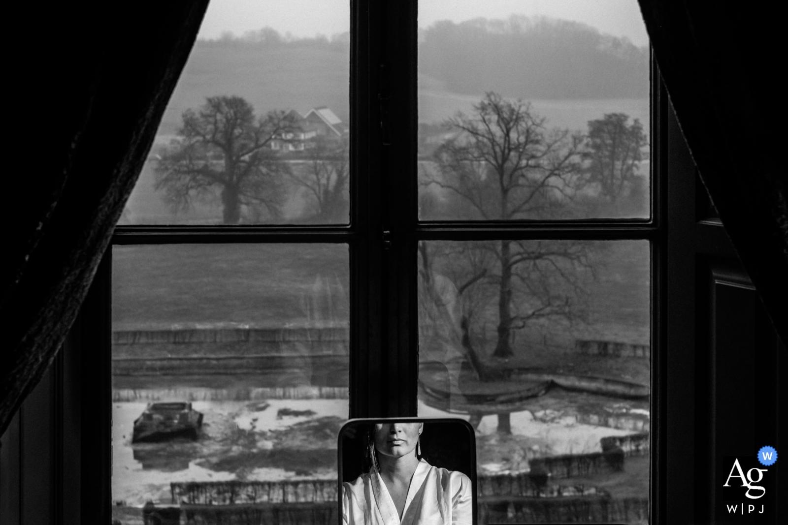 Braut, die sich im Chateau Neercanne Maastricht mit einem kleinen Spiegel im Fenster fertig macht
