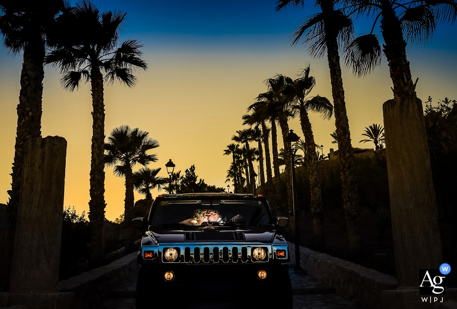 Murcia Spain wedding photographer   Wedding Sunset portraits of the bride and groom in a hummer with silhouetted palm trees
