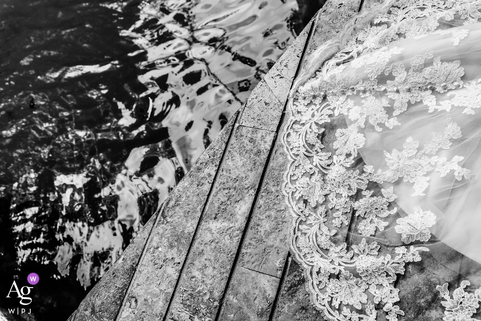 Wedding photographer for the Hotel Xcaret Mexico | Wedding dress detail against the wood Dock and water in black-and-white