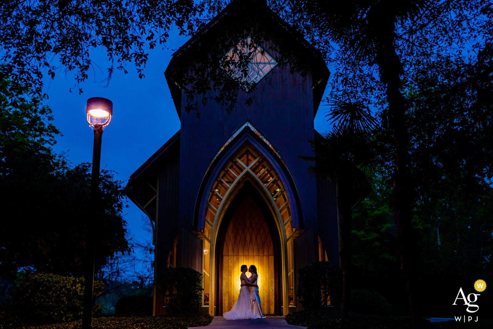 Baughman Center, University of Florida Gainesville Wedding Photography |  Brides pose for a portrait in front of their ceremony location at dusk, backlit against the building