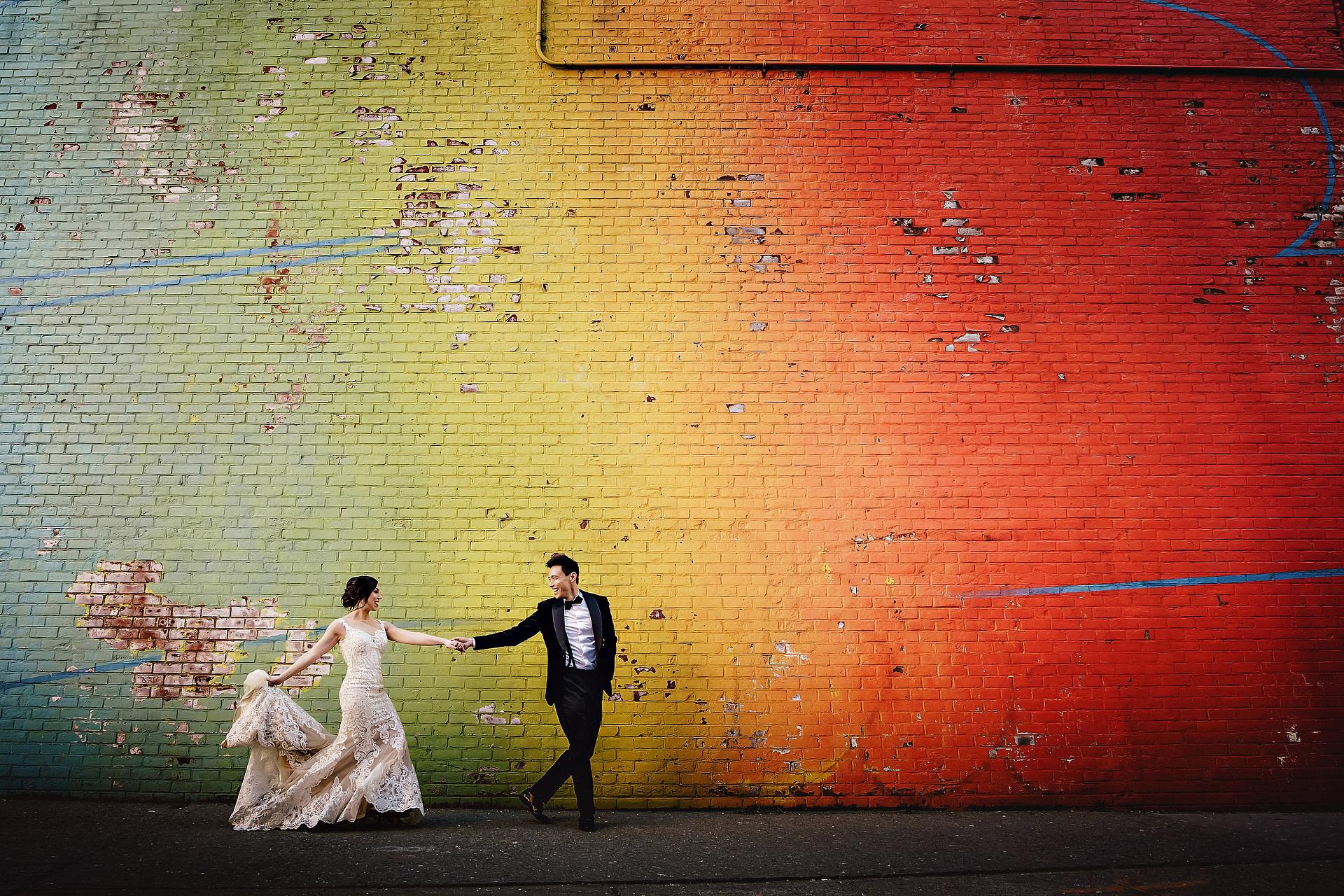 Creatieve portretten en trouwreportages Bruid & bruidegomportret die voor kleurrijke muur buiten lopen