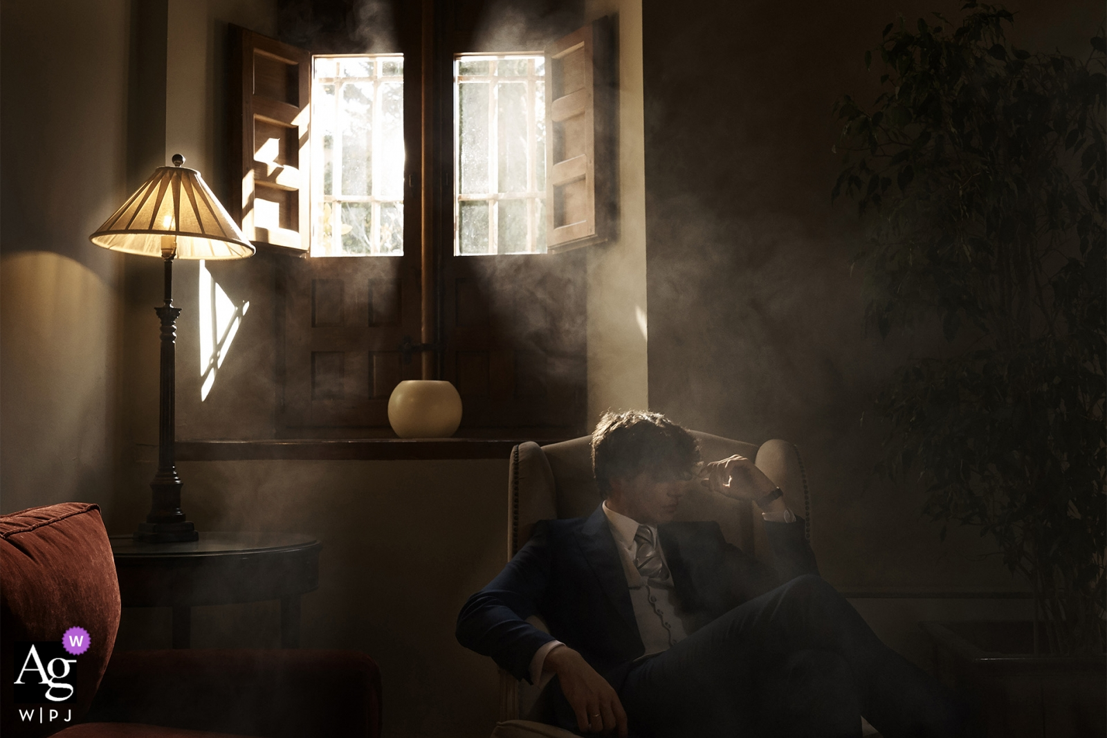 Spain wedding photographer shot this portrait of the groom as he sits in a dark, smoky room before his Valencia wedding