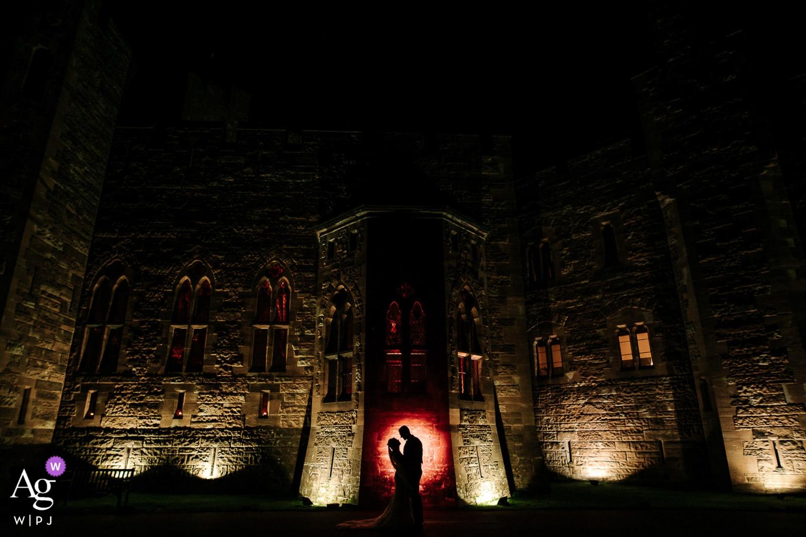 De bruiloftsfotograaffotograaf van Engeland ontwierp dit portret van de bruid en bruidegom die 's nachts voor het Peckforton Castle staan