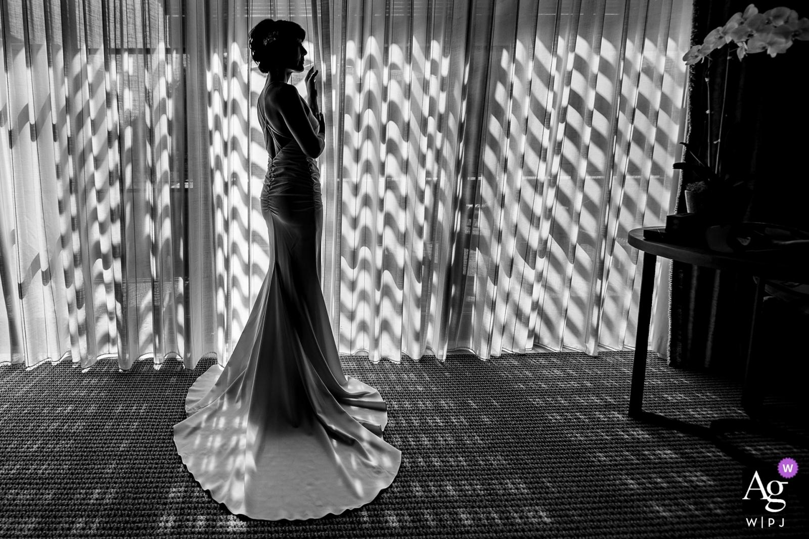 Dit zwart-witte silhouetfoto van de bruid die voor de ramen stond, werd gevangen genomen door een huwelijksfotograaf uit Noord-Californië in San Francisco