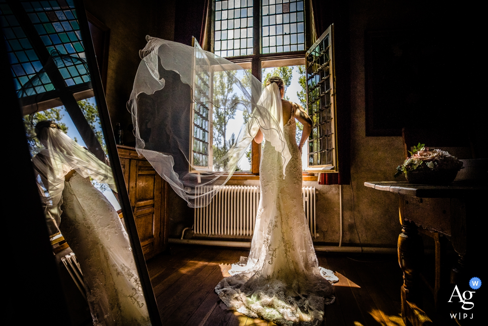 Zuid Holland wedding photographer captured this moment as the wind blew the brides veil as she stood in front of an open window in Kasteel Dussen