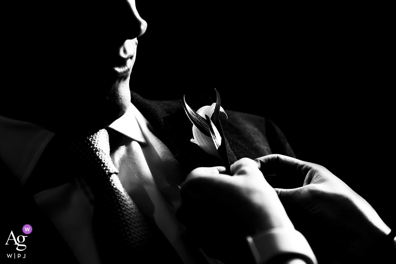 Schwarzweiss-Foto des Bräutigams, der seinen Boutonniere an feststecken lässt.