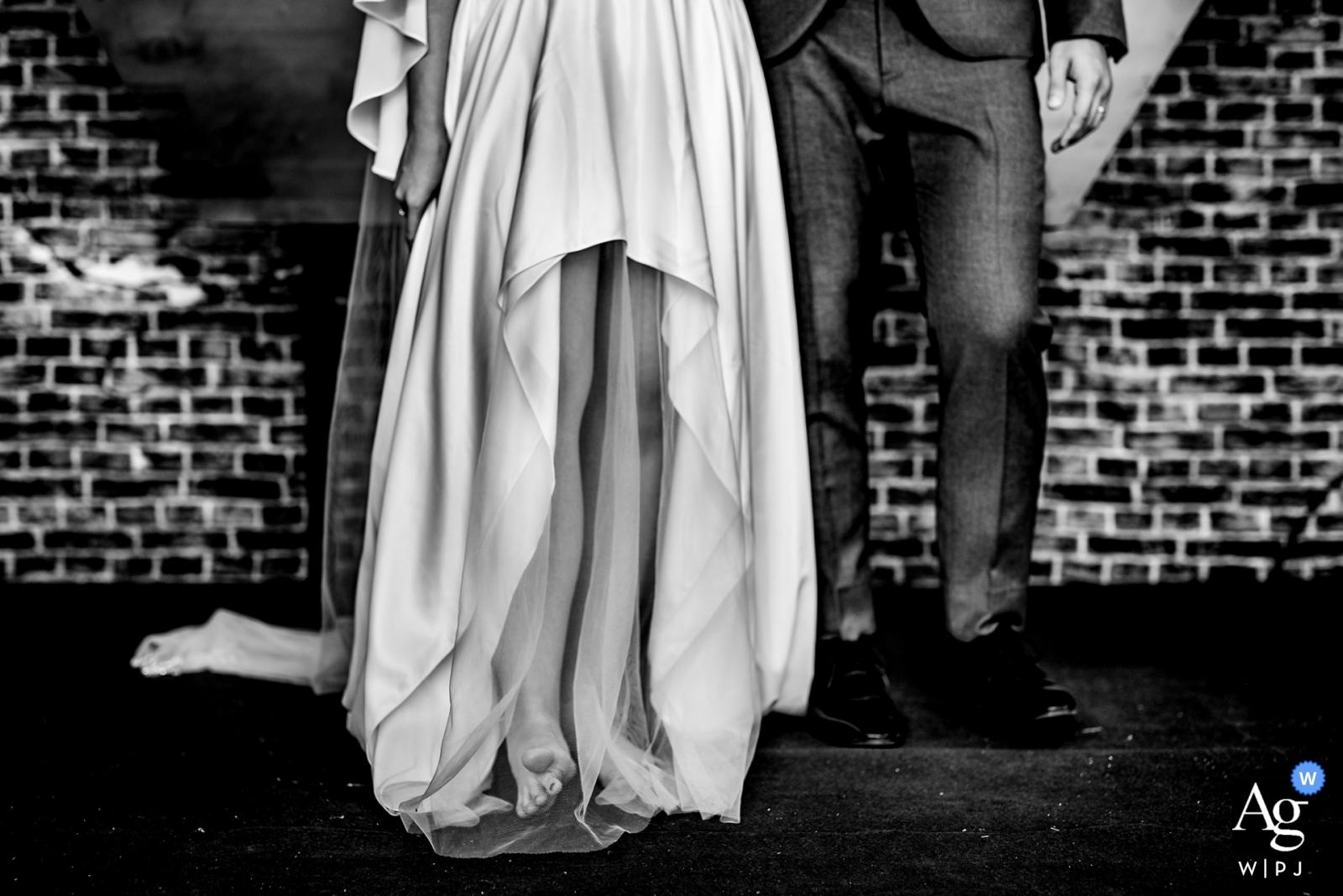 La photographe de mariage de Phu Quoc a conçu cette image en noir et blanc des jambes des mariés lorsqu'ils se tiennent debout après la cérémonie