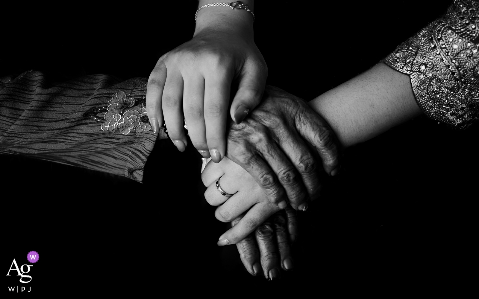 Detail wedding photograph of a grandmother grabbing the hand of the bride in Guangdong