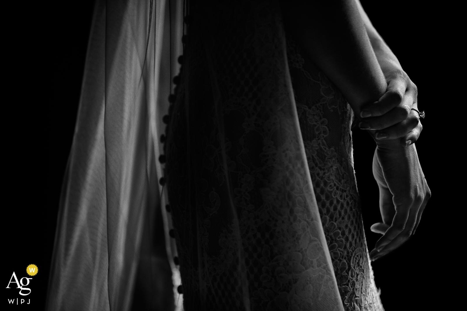 Un photographe de mariage de Toscane a créé cette image de détail en noir et blanc de la robe et du voile en dentelle de mariées