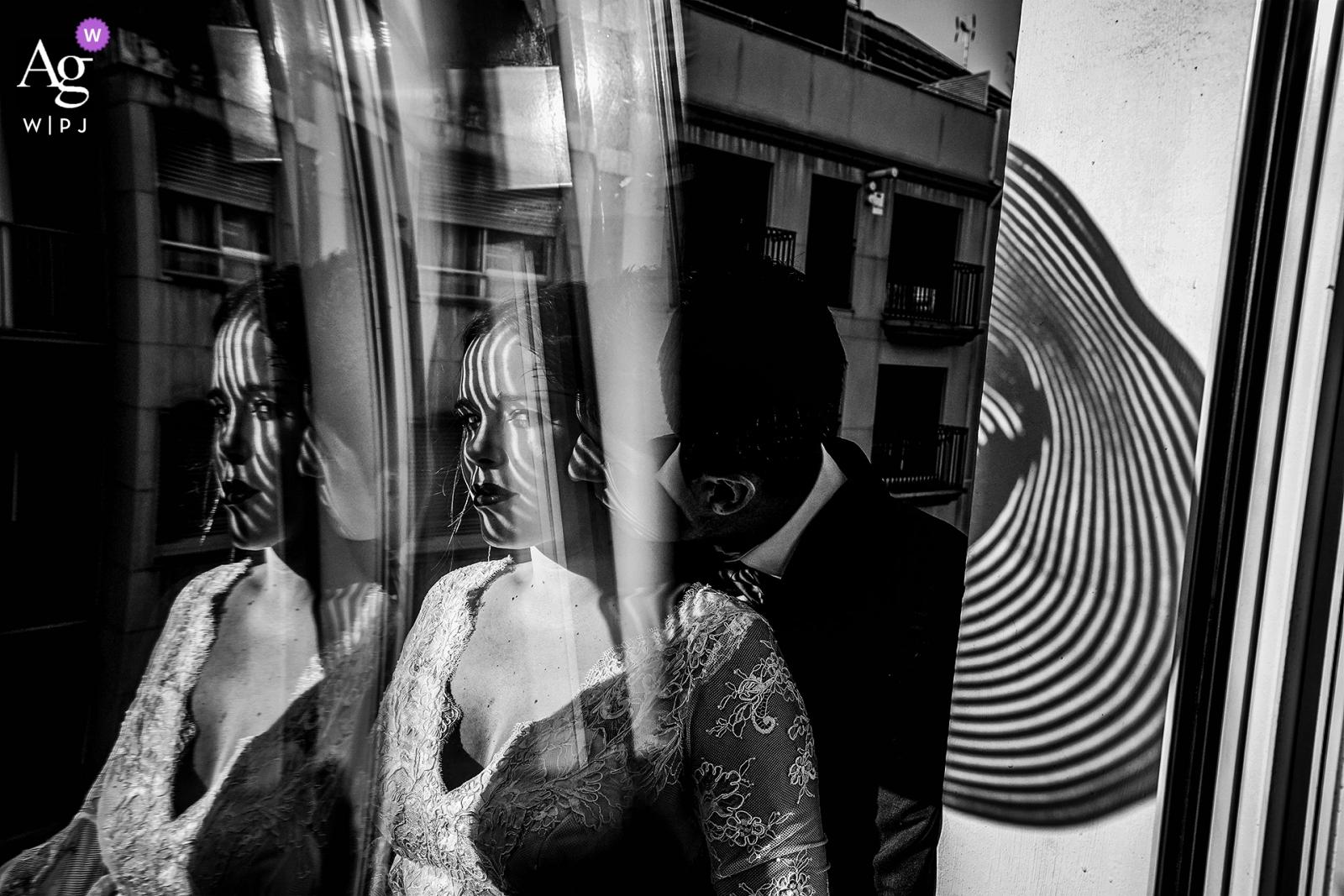 Mariée et le marié de la Puerta De Jeronimos dans une pièce ensoleillée, tirant à travers une vitre le jour de leur mariage
