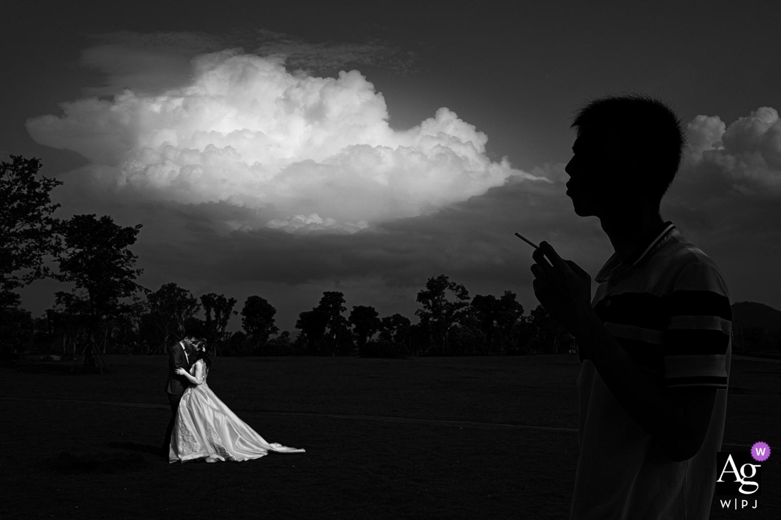Fotograf ślubny Nanping wykonał ten czarno-biały portret ślubny, podczas gdy gość weselny stoi na pierwszym planie