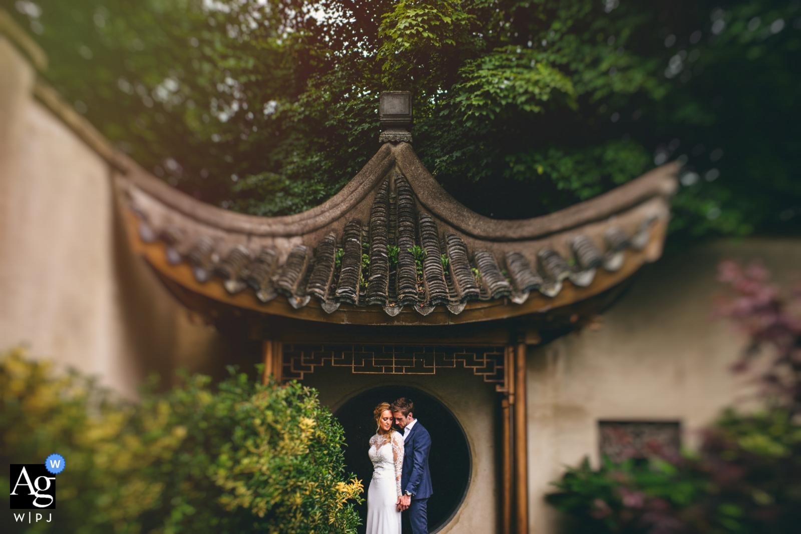 Martra Centre - Fotos de la boda en el Reino Unido - Una pareja abrazándose desde atrás en el arco japonés