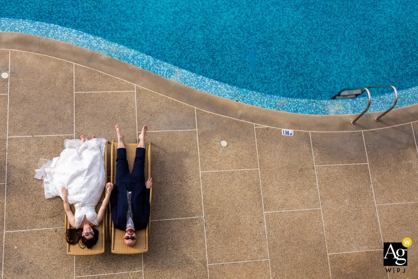 De huwelijksfotograaf van Venezuela ving dit luchtfoto van de bruid en bruidegom die aan het zwembad ontspannen in hun huwelijkskledij