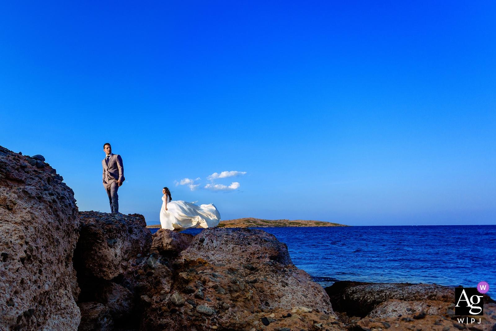 Fotograf ślubny Attica wykonał ten ślubny portret młodej pary stojącej na wietrznym klifie nad błękitnym morzem