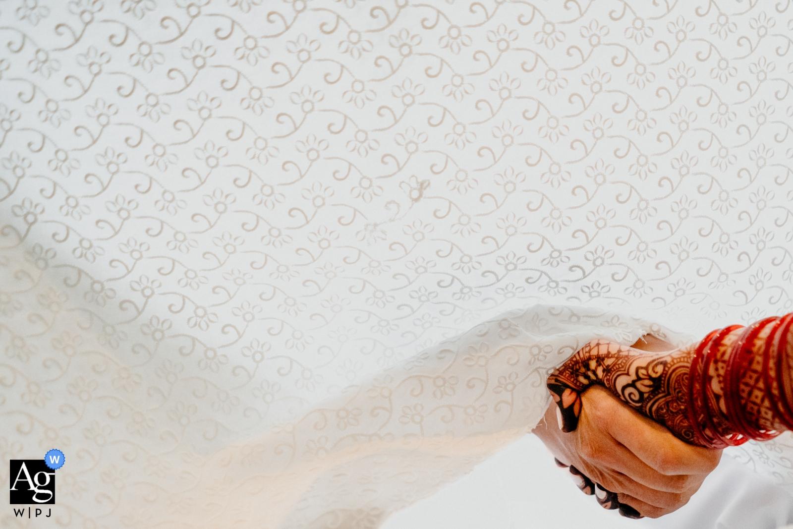 Dieses Detailbild des Händchenhaltens der Braut und des Bräutigams durch einen Vorhang während ihrer Zeremonie wurde von einem Ontario-Hochzeitsfotografen geschaffen