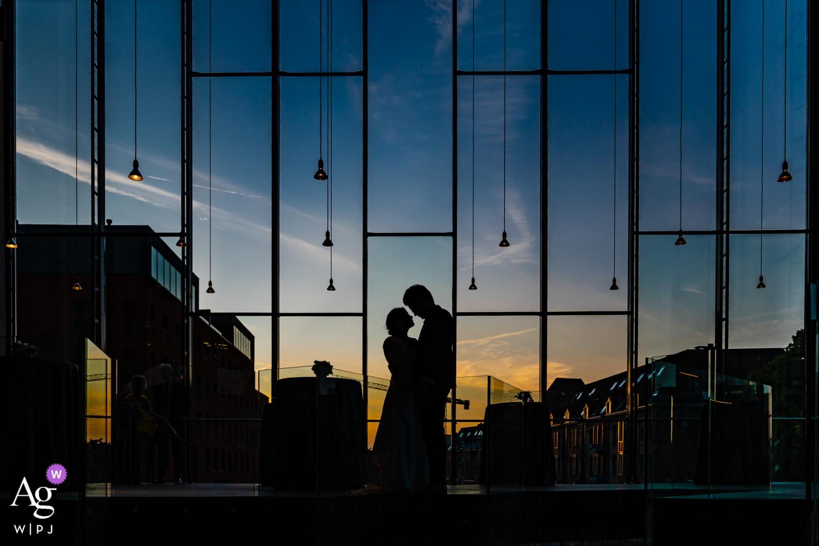 Este retrato de silhueta da noiva e do noivo em frente a uma parede de vidro ao pôr do sol foi desenhado por um fotógrafo de casamento de Flandres