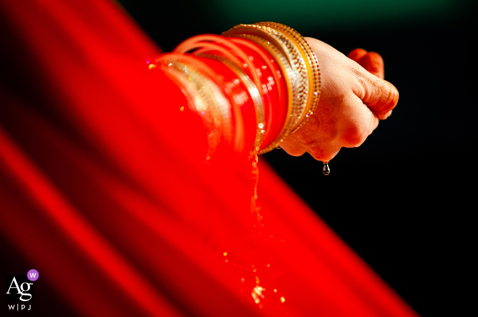 London wedding photographer shot this detail photo of water dripping off the brides hands and bangled covered wrists
