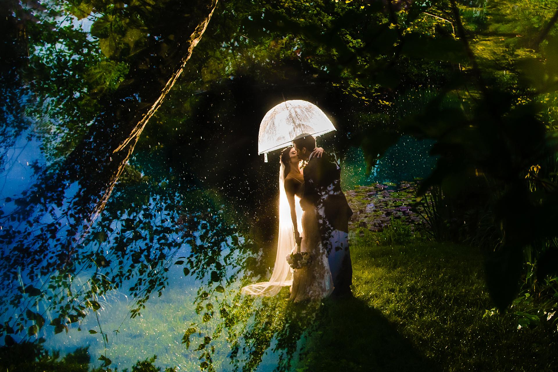 Fotograaf had een goed idee voor dit bruidspaarportret onder regenparaplu.