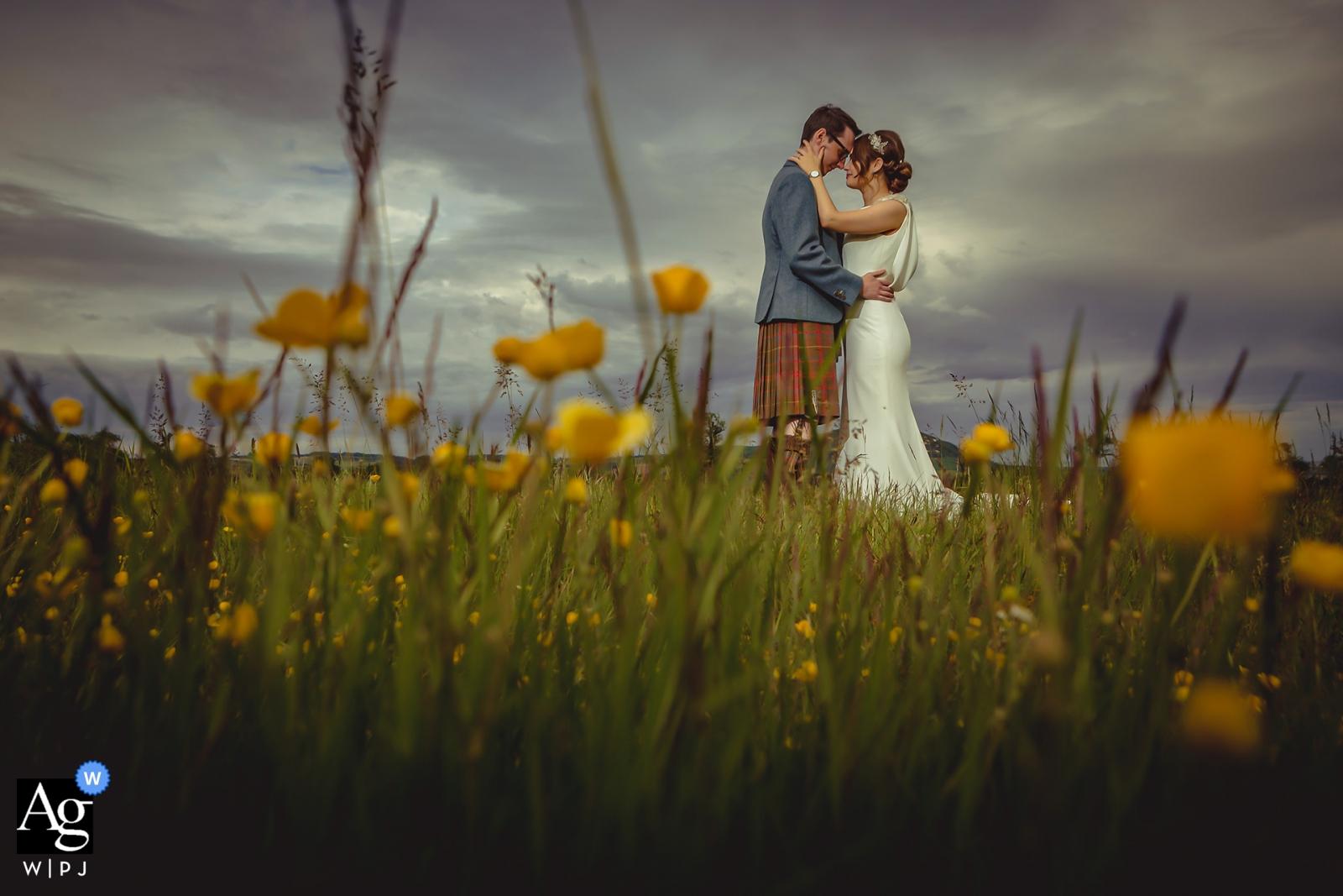 Schottland-Hochzeitsporträt von die Braut und der Bräutigam schossen durch langes Gras. Leuchtet bei ausgeschaltetem Kamerablitz.