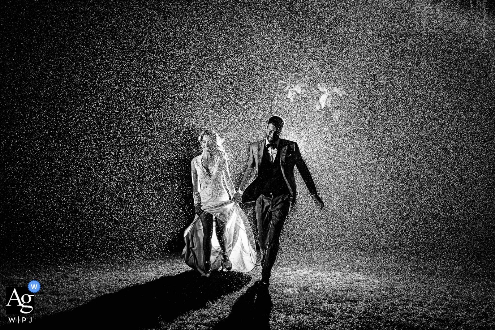 Schwarzweiss-Bild Tenuta di Polline der Braut und des Bräutigams, die durch den Regen laufen