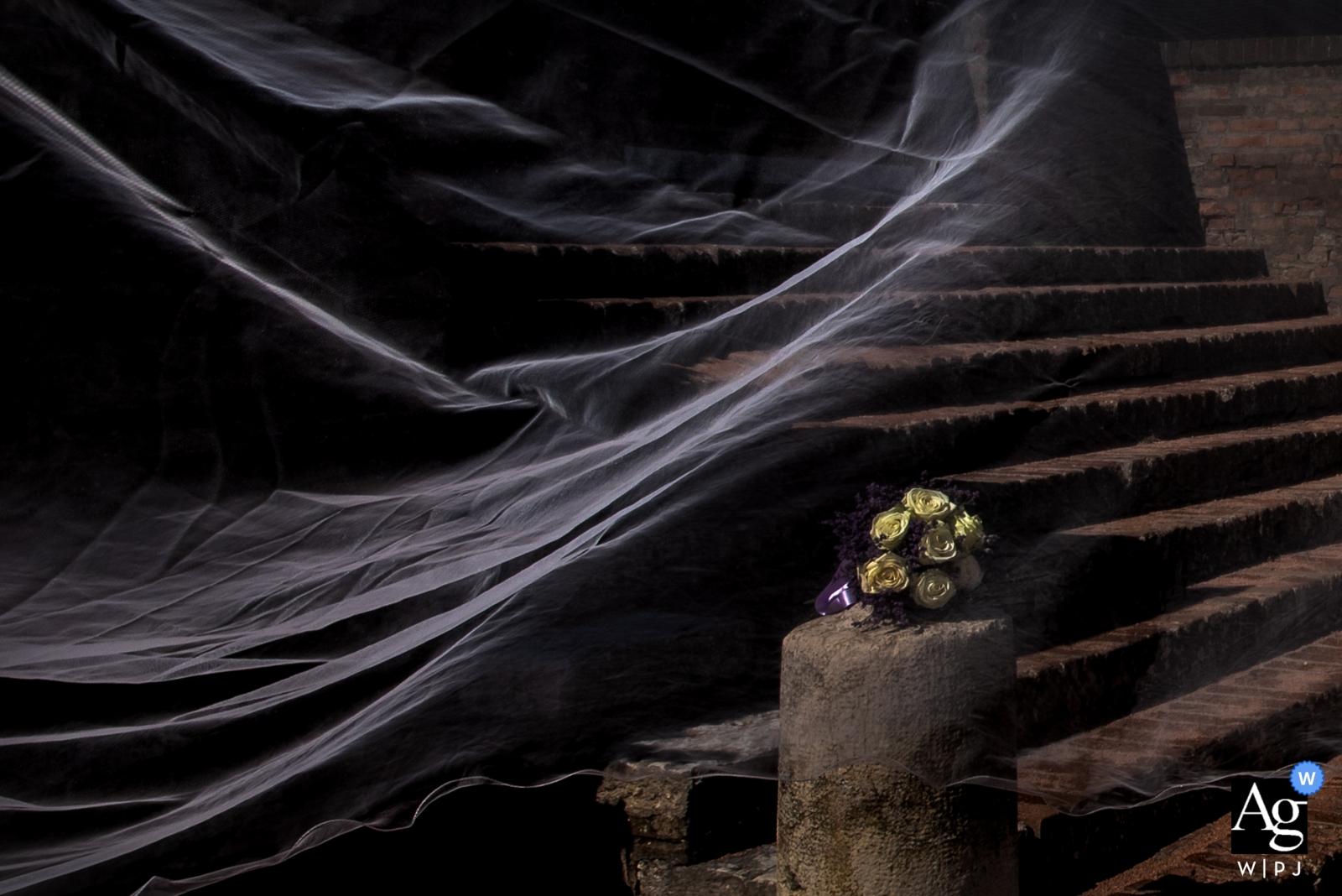 Image de détail de mariage du bouquet et du voile de la mariée par une journée venteuse au Castello di San Giorgio