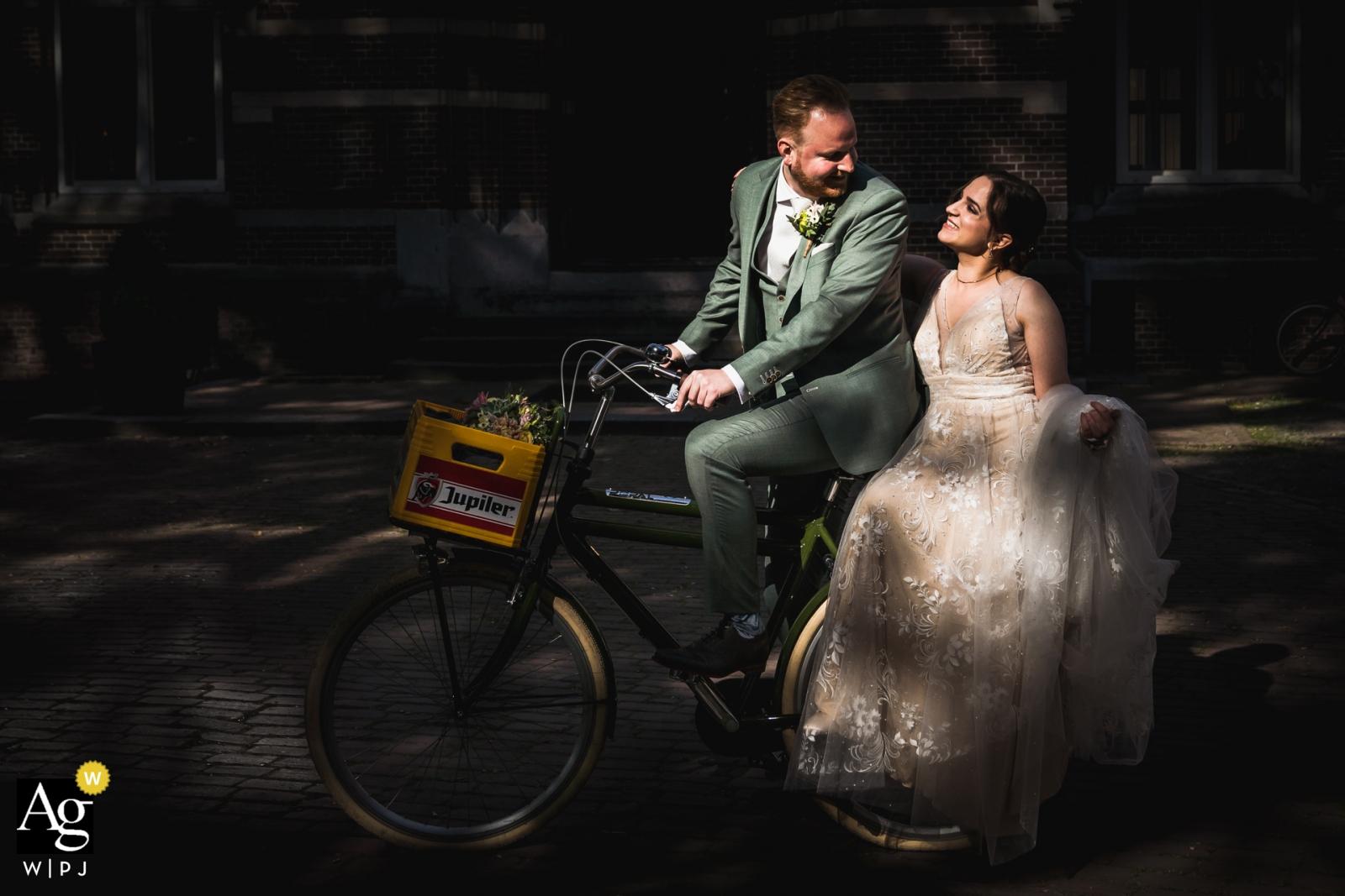 Bovendonk, Hoeven Venue portret ślubu pary młodej przybywającej na miejsce na rowerze
