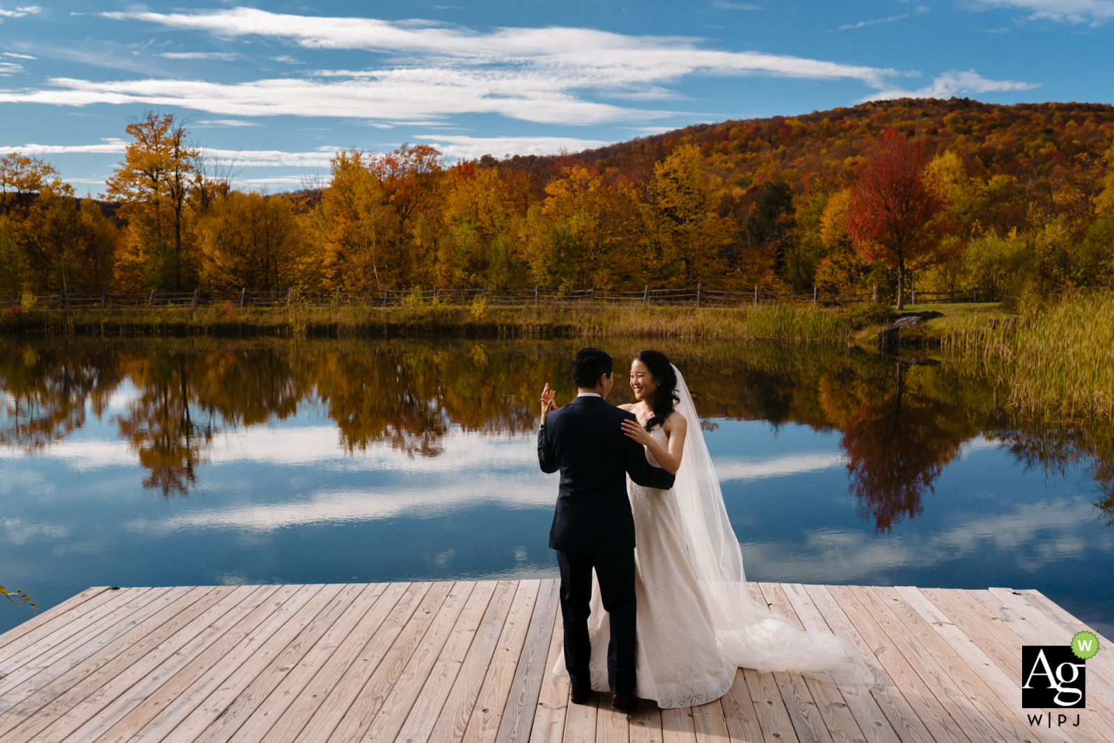 The Ponds at Bolton Valley, Vermont Venue Photo | Wedding couple dancing on a lakeside dock with fall leaves reflecting behind them