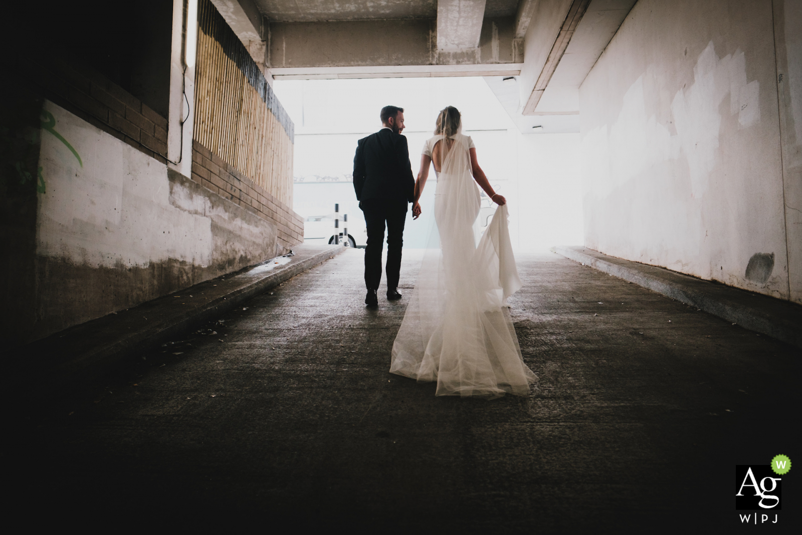 Wedding Photography at The Merchant Hotel, Belfast, Northern Ireland. | The bride and groom pictured emerging from an industrial-looking area in the city centre.