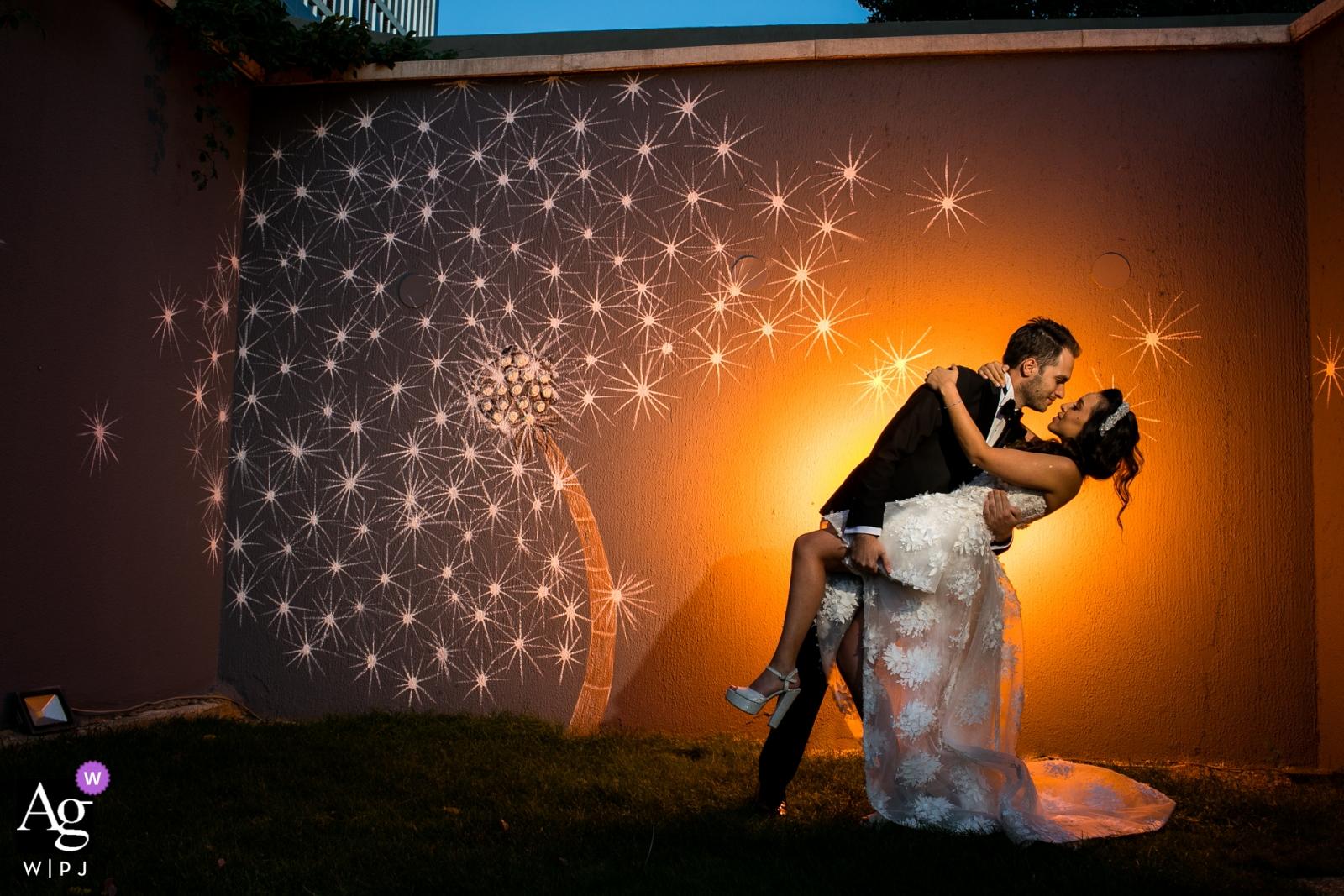 Fotografia ślubna Wyndham Ankara - Pan młody trzyma pannę młodą ze swojego biodra tuż przy ścianie z fototapetą z kwiatami i wyróżnia się pomarańczowym kolorem