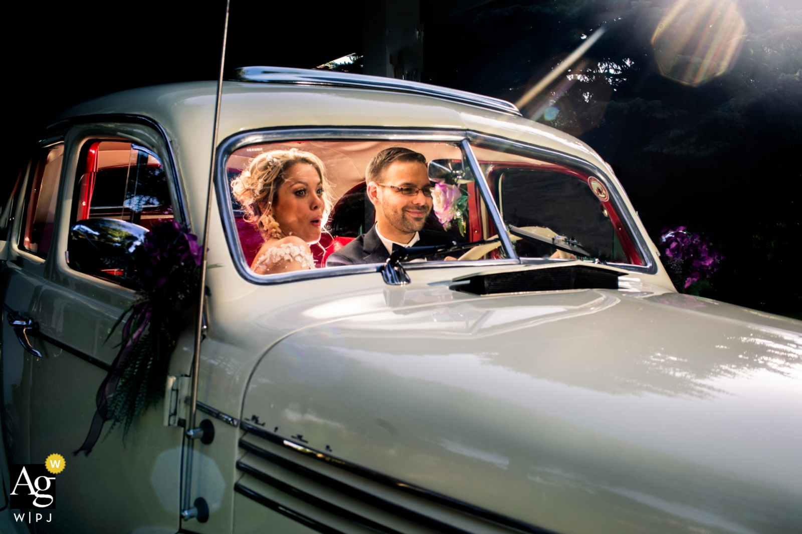 İncek Garden, Ankara wedding photographer: Bide and groom in a vintage car highlighted with an inside flash are pretending like they are driving