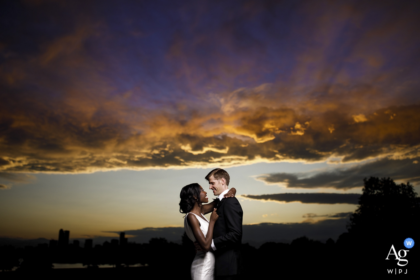 Bride and groom take a photo portrait together as the sun sets behind them at the Denver Museum of Nature and Science