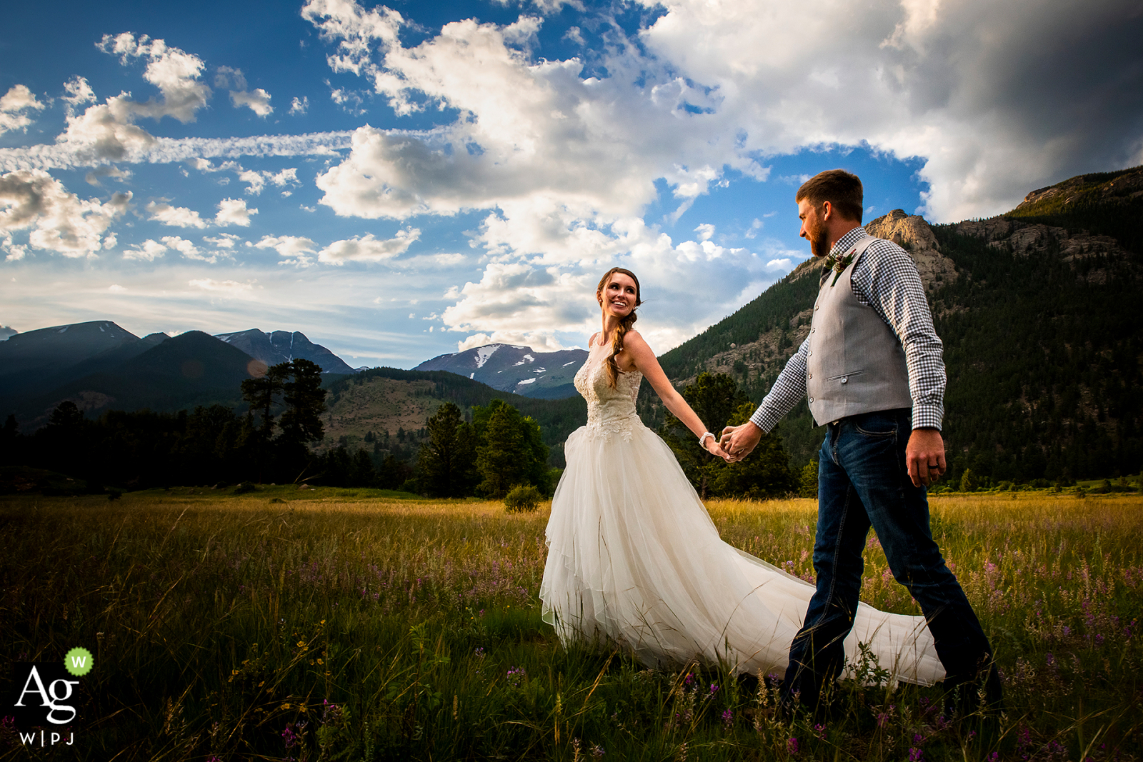 Bride and groom walking through meadow for a wedding portrait at the Rocky Mountain National Park (Estes Park, CO)