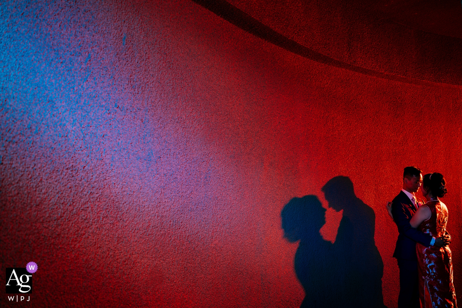Pomona, Ca Bride and groom creatively lit during wedding portrait session against wall of red.